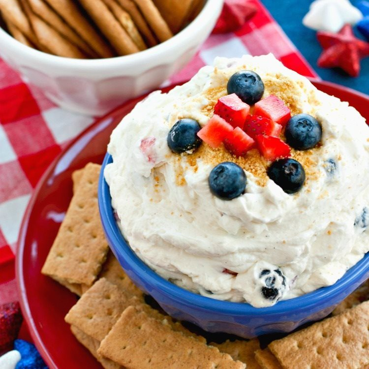 Red, White, and Blue Cheesecake Dip in a blue bowl that's on a red plate.
