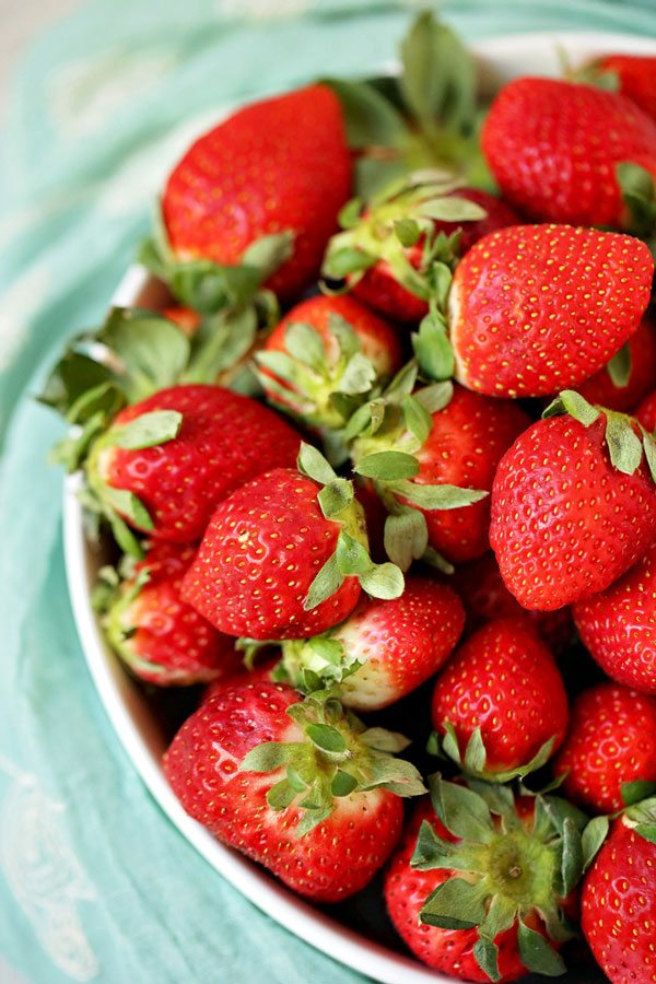 Strawberries stacked in a white bowl.