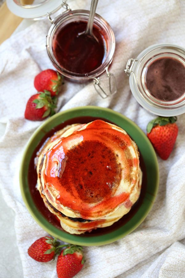 Overhead shot of a stack of pancakes with strawberry syrup.