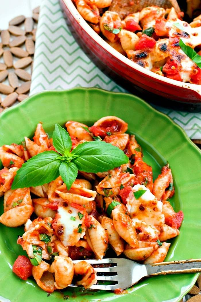 Caprese baked pasta on a green plate.