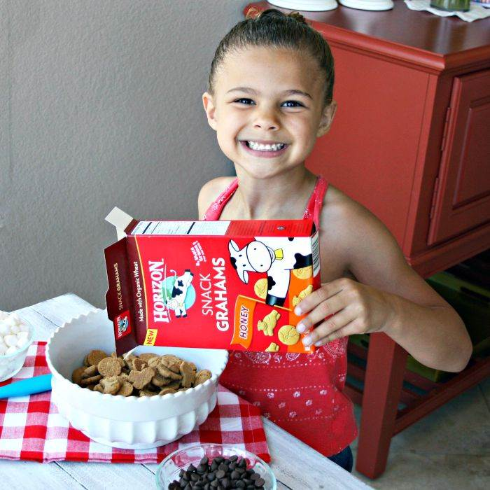 A girl helping to make Easy S\'mores snack mix