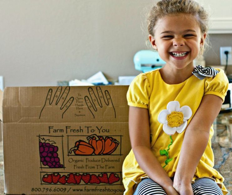 Cute little girl sitting on the kitchen counter with a produce delivery box behind her.