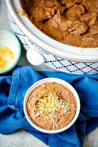 A bowl full of refried beans with a slow cooker in the background full of more refried beans.