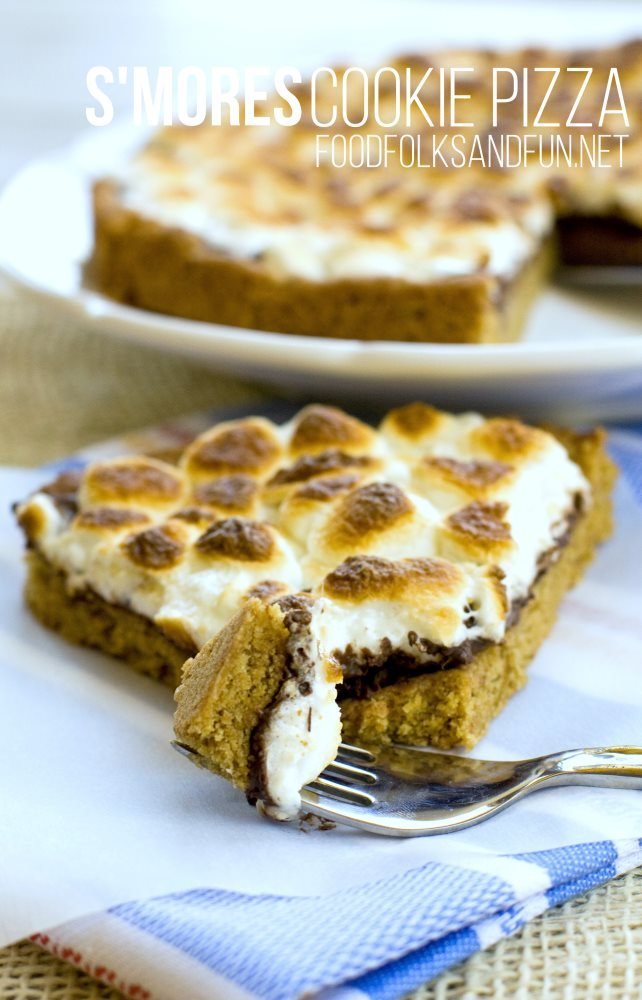S'mores Cookie Pizza recipe – this pizza has a graham cracker cookie crust, melted milk chocolate, and toasted marshmallows! You can make this S'mores Cookie pizza in less than 30 minutes! #smorefun #smores via @foodfolksandfun
