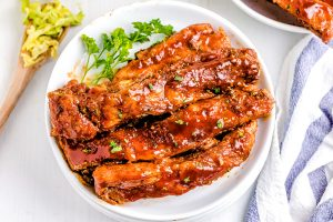 Cut spare ribs on a white plate with coleslaw in the background.