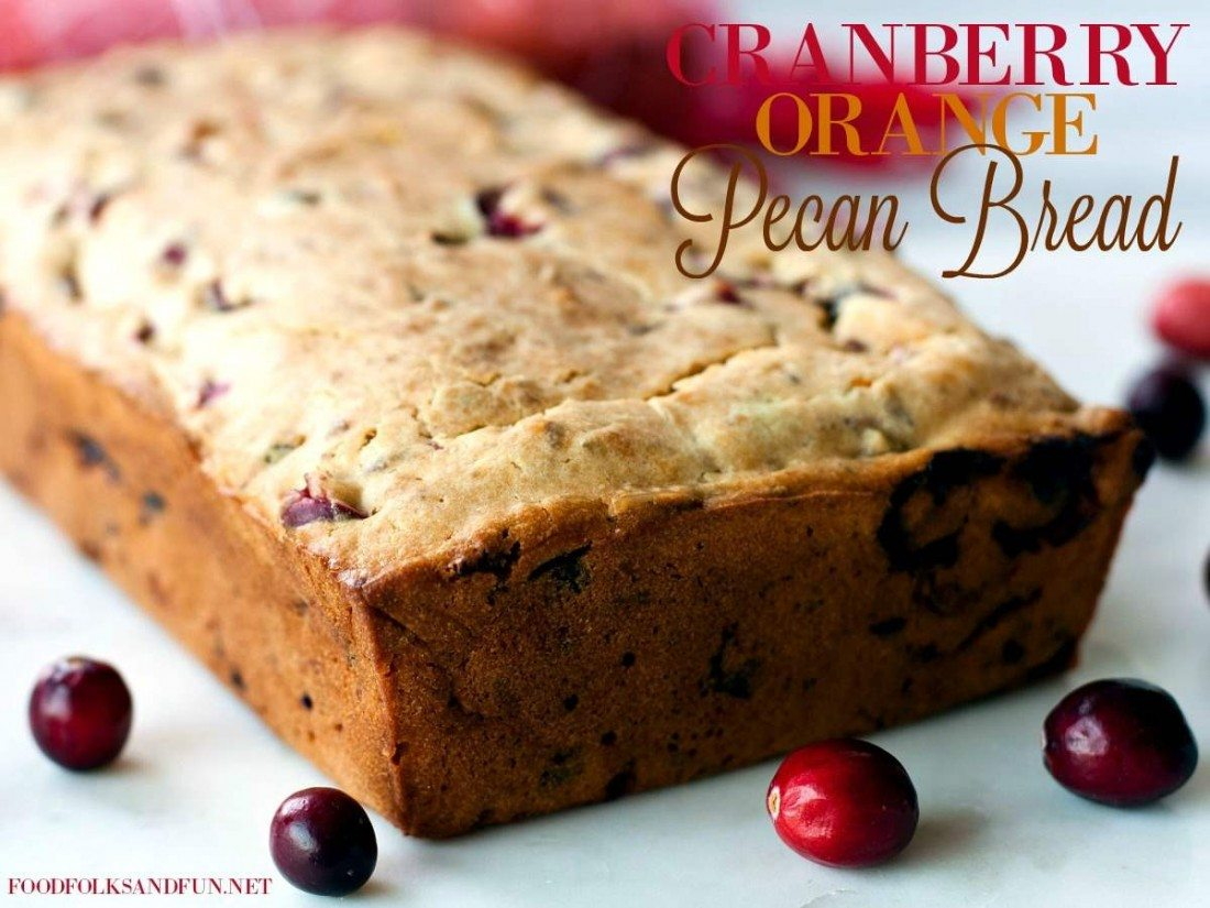 A full loaf of cranberry orange bread with cranberries around it.