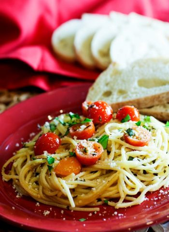 Tomato Basil Pasta on a plate with a side of bread