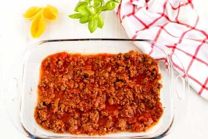 Spread half of the meat sauce into th bottom of a 9x13-inch pan.