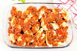 Cover the stuffed shells with half of the meat sauce and shredded cheese.