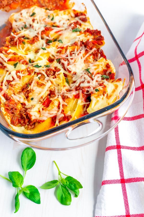 A pan full of stuffed shells and meat sauce.