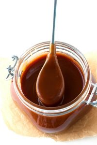 A spoonful of caramel sauce from a jar full of caramel