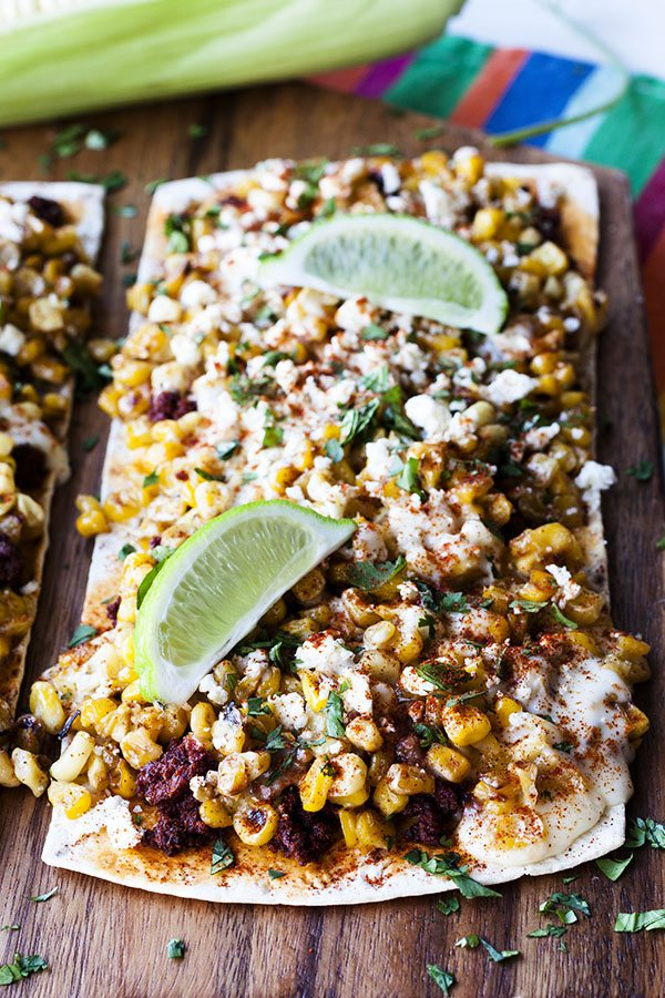 A cutting board with Mexican Street Corn Flatbread Pizza on top