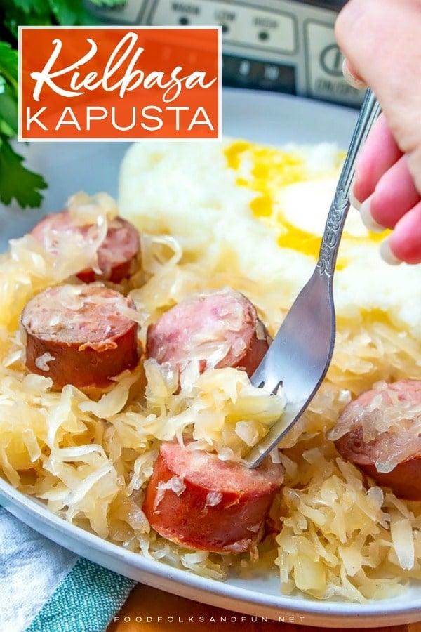 A plate full of kielbasa kapusta with text overlay for Pinterest.