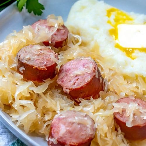 Close up picture of kielbasa kapusta on a serving place with mashed potatoes.