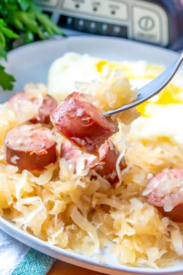 Serving kielbasa kapusta on a white plate.