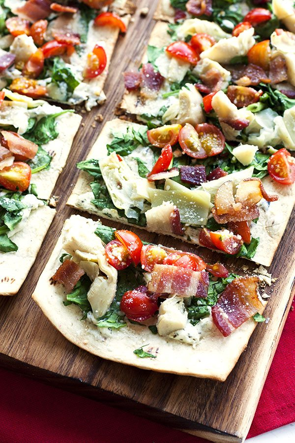 Slices of Grilled Spinach Artichoke Flatbread on a wood plank