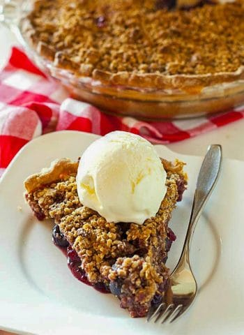Cherry pie on a white plate with a scoop of vanilla ice cream.
