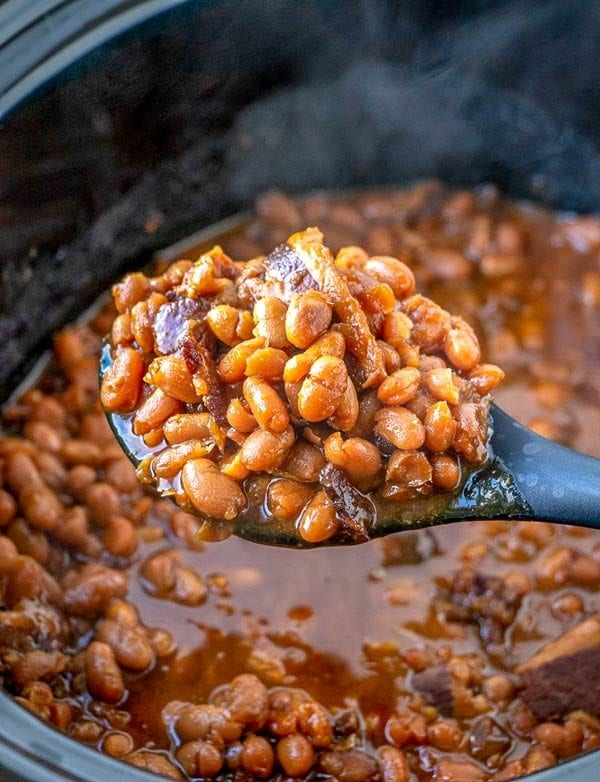 Finished baked beans in a slow cooker with a spoon.