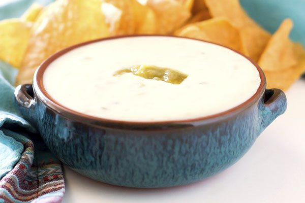A bowl full of green chile white queso dip that is garnished with green chile.