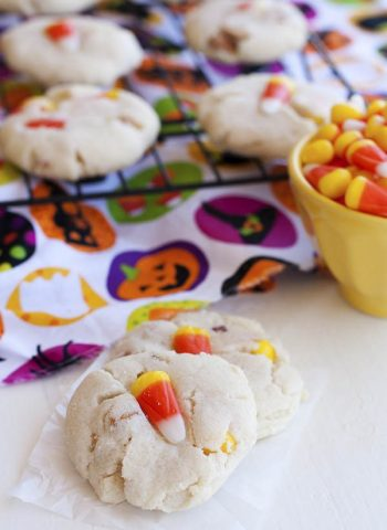 Two candy corn cookies on the counter with more on a wire rack