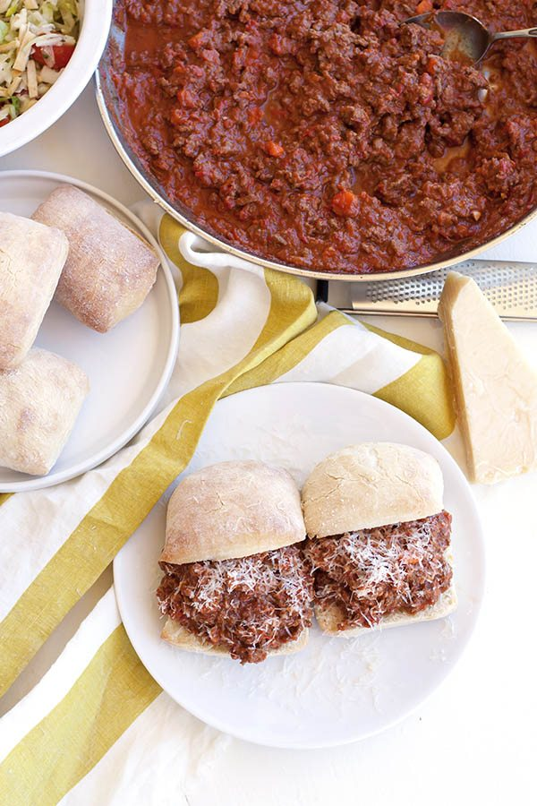 Top view of Easy Beef Bolognese Sloppy Joes with rolls and filling in the background