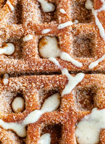 A close up overhead picture of the finished pumpkin churro waffles with cream cheese glaze.