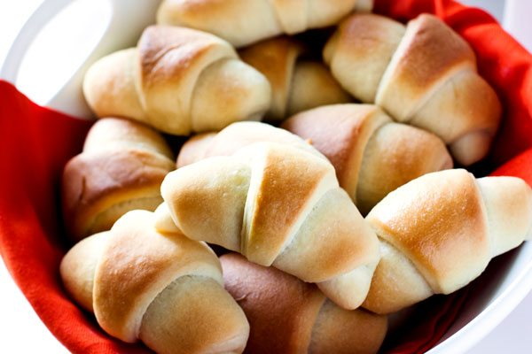 An overhead picture of crescent rolls in a white serving bowl.