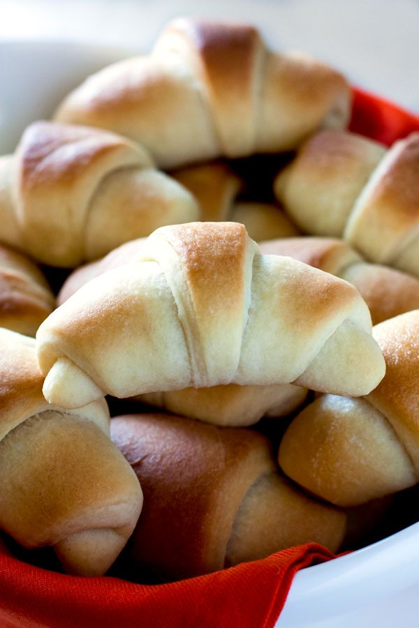 A pile of crescent rolls in a serving bowl.