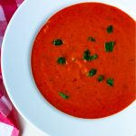 A close up picture of easy tomato soup garnished with basil.