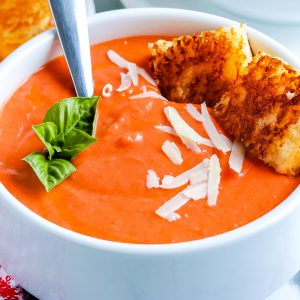A close up picture of homemade tomato soup in a white bowl.
