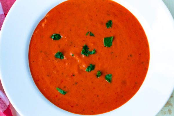 An overhead picture of tomato soup in a white bowl.