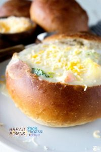 A bread bowl filled with creamy vegetable soup.