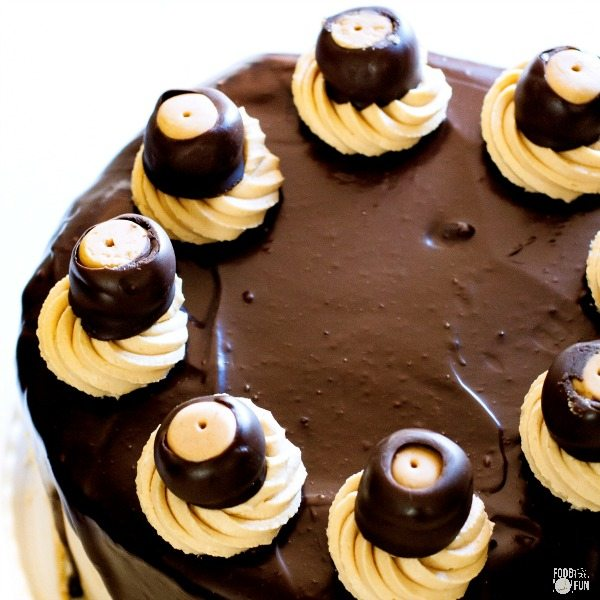 This cheesecake cake has 2 layers of fudgy brownies, 1 layer or luscious peanut butter cheesecake, fluffy peanut butter frosting, silky-smooth chocolate ganache, and luscious buckeye confections. All of these elements make this Buckeye Brownie Cheesecake Cake simply irresistible!