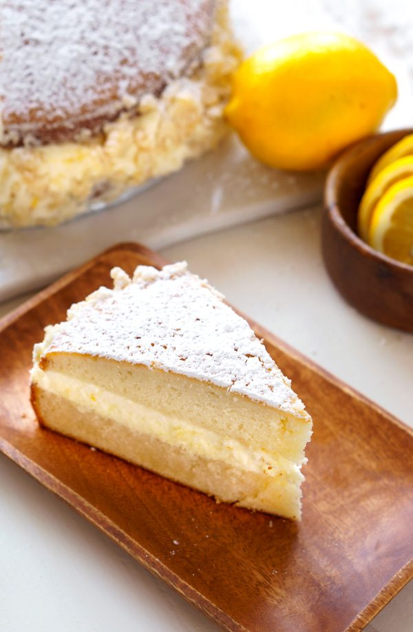 A top view of a slice of Copycat Olive Garden Lemon Cake on a wooden serving plate