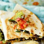 A veggie quesadilla topped with salsa and guacamole