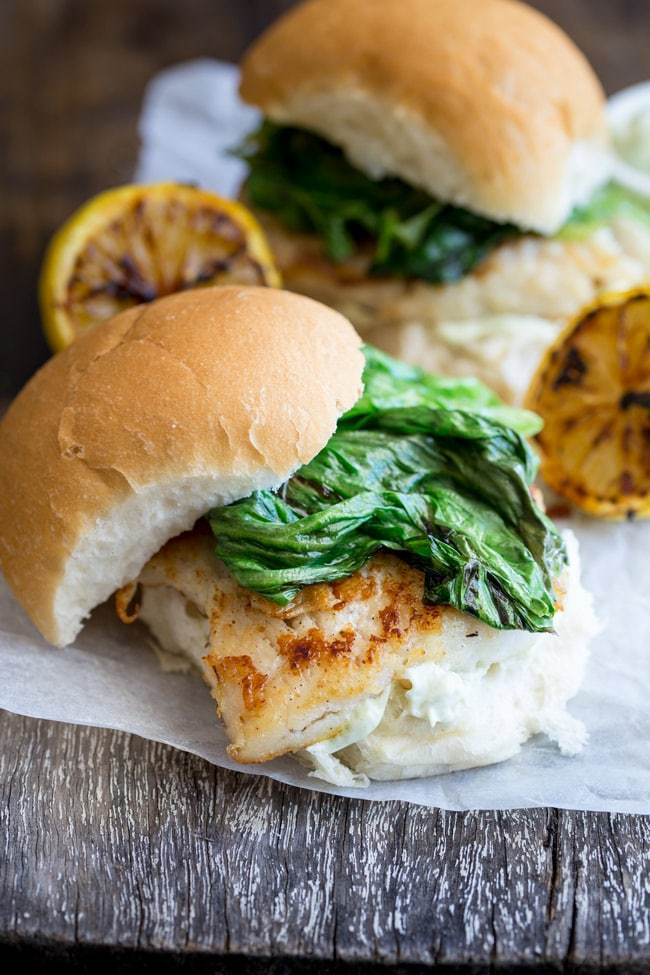A fish burger with charred lettuce and tarragon mayo on parchment paper
