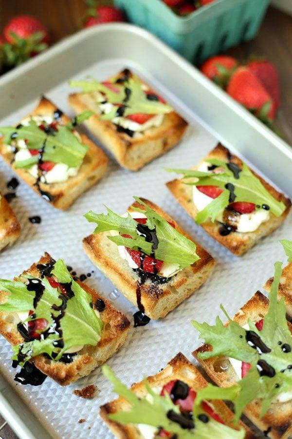 Pieces of Strawberry Goat Cheese Bruschetta on a no-slip baking mat on a baking sheet