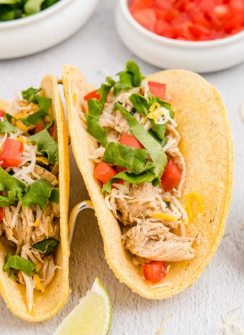 The finished Crockpot Shredded Chicken Tacos with lettuce and tomatoes on them.