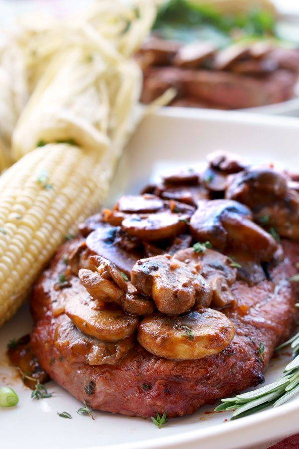 Grilled Steak marsala on a plate with a side of corn on the cob