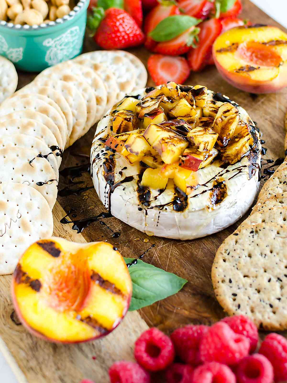 A bowl of grilled brie with peaches and honey and balsamic dressing with crackers