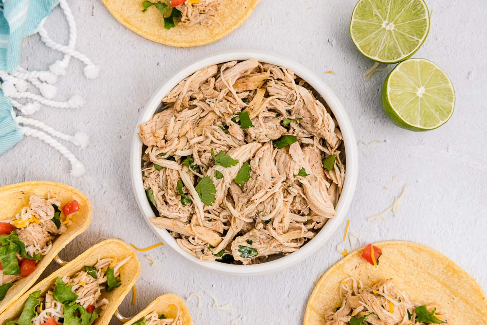 An overhead picture of the finished Crockpot Shredded Chicken Tacos with shredded chicken in a bowl.