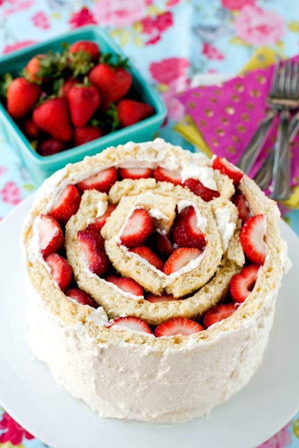 Rolled Up Strawberry Shortcake Cake on a white cake pedestal.