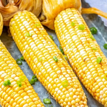 3 pieces of smoked corn with husks on with green onions.