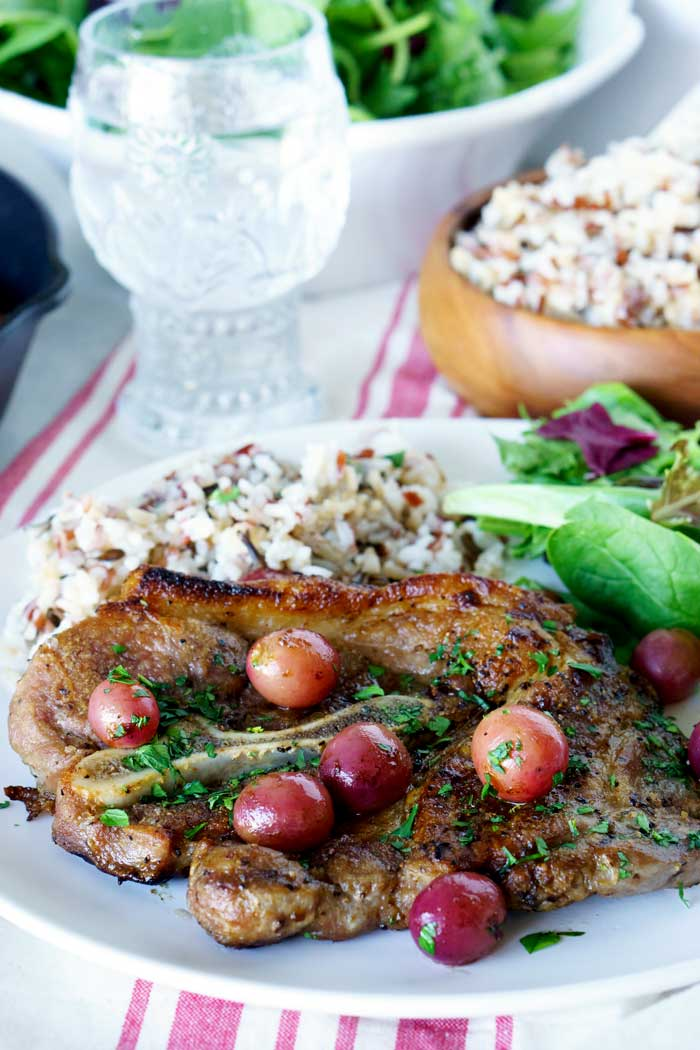 Skillet Pork Chops with grapes and caramelized shallots on a plate with a side salad and rice