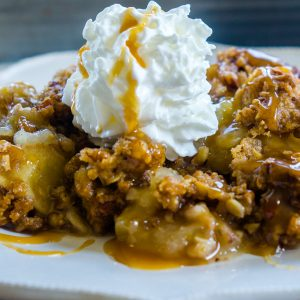 Apple Crisp on a plate with caramel sauce drizzled on top.