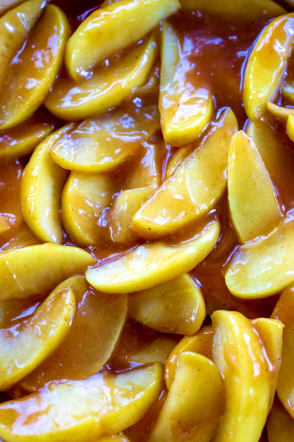 How do you make fried apples? First, you cut the apples and simmer them in a butter, apple juice, and spice mixture until they're for-tender. Then, move the apples to a serving dish using a slotted spoon. Then, thicken the warm apple juice left in the bowl with corn starch. Next, whisk constantly until the mixture thickens. Finally, pour the sauce over the fork-tender apples and toss until the apples are coated.