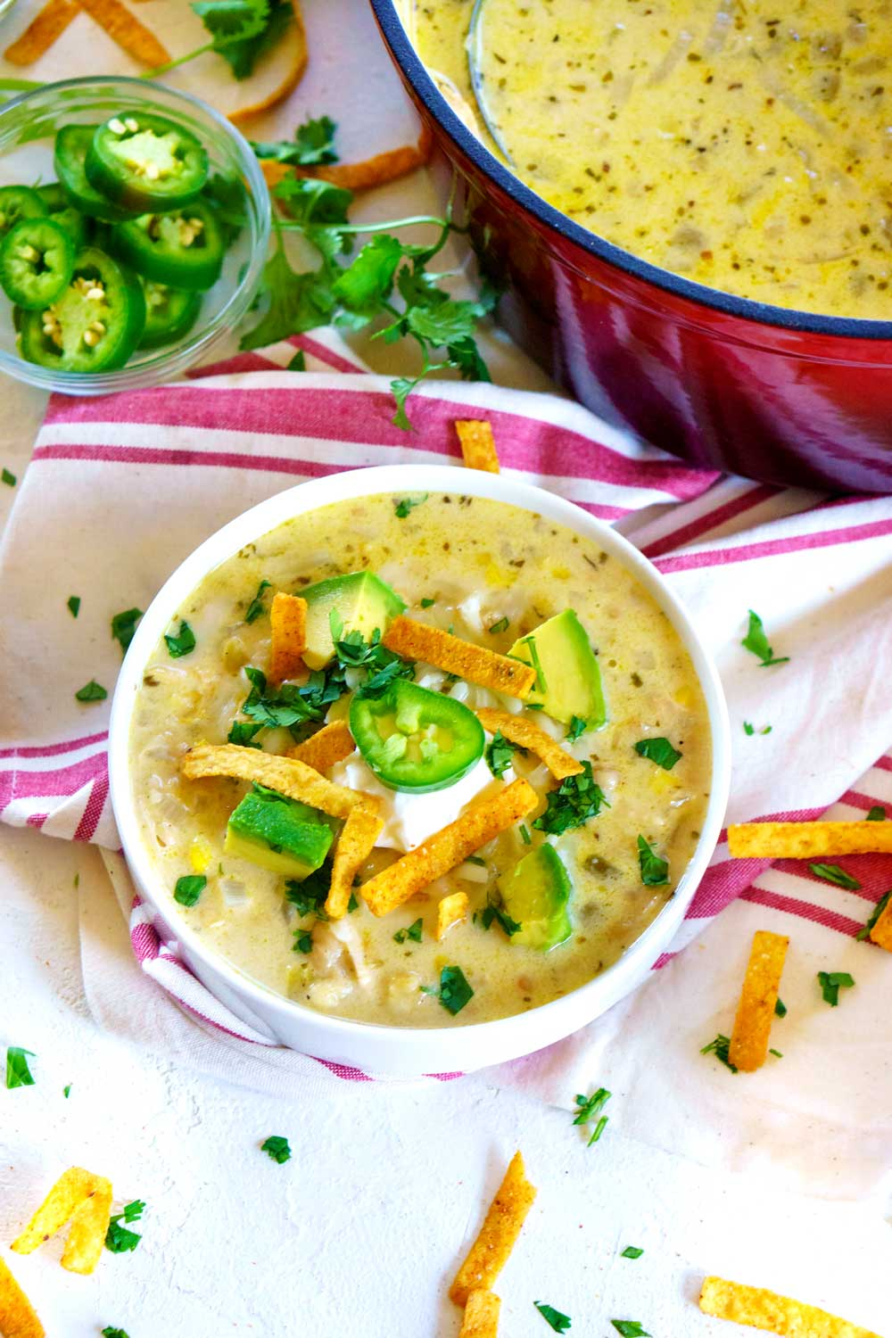 Are you ready for one of the easiest recipes for White Chicken Chili out there? First, in a large pot, sauté the onions and garlic in a little bit of butter. Next, add all of the other chili ingredients and bring the mixture up to a low boil. Then, reduce the heat to simmer the chicken chili for about 10 minutes. Finally, stir in the shredded cheese and sour cream until everything is good and melted, then serve!