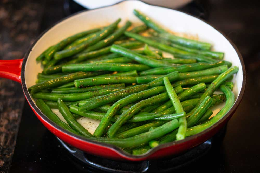 The finished green beans in a red skillet.