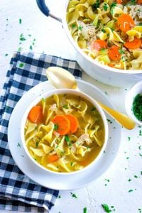 Overhead picture of chicken noodle soup in a white bowl and in a pot.