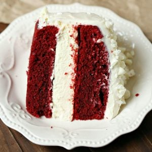 A close up picture of a slice of red velvet cheesecake on a white plate.